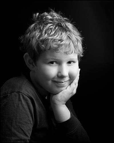 Noir, black background portrait of young boy