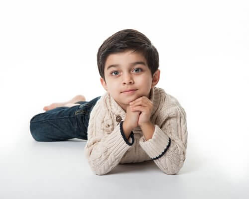 young boy, laying on floor looking at camera